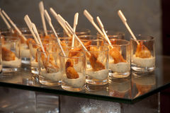 Breaded scampi in snifter with cream. Fried scampi on wooden sticks in snifter with cocktail sauce on glossy black glass Royalty Free Stock Photo