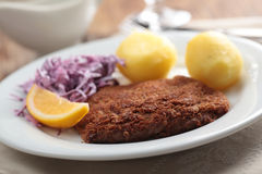 Breaded schnitzel with potato Stock Photo