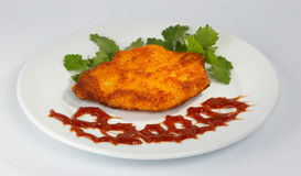 Breaded Steak and Ketchup. Breaded rump or round steak, ketchup and greens on a white plate. Also called country fried steak Royalty Free Stock Photos