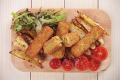 Breaded veggie sticks. With roasted potato on wooden board Royalty Free Stock Image