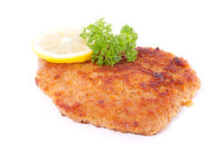 A breaded wiener schnitzel. With lemon and parsley isolated over white Stock Images