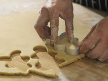 Breadman cutter. Chef cutting the ginger breadman from the dough Royalty Free Stock Photography