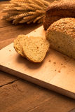 Breads on chopping board. Bread on chopping board and rustic tabletop background Royalty Free Stock Photo