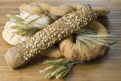 Breads on a mat. Different types of bread and some wheat on a bamboo mat Stock Photos