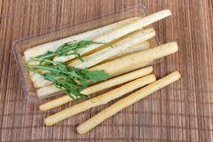 Breadsticks with Italian herbs in container with arugula leaves. Breadsticks with Italian herbs seasoning, also known as grissini, in transparent plastic stock image