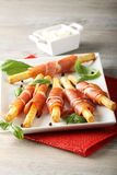 Breadsticks with raw ham and cheese. On complex background Royalty Free Stock Images