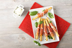 Breadsticks with raw ham and cheese. On complex background Stock Photography