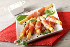 Breadsticks with raw ham and cheese. On complex background Stock Images