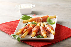 Breadsticks with raw ham and cheese. On complex background Royalty Free Stock Photography