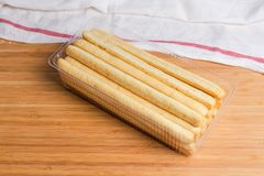 Breadsticks with sesame seeds in plastic container on wooden surface stock photos