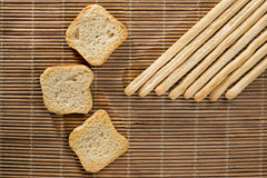 Breadsticks and toasts. A row of breadsticks and toasts on a wicker mat Stock Image