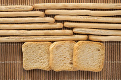 Breadsticks and toasts. Rows of breadsticks and toasts on a wicker mat Stock Photos