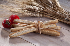 Breadsticks, tomatoes and ears of wheat Royalty Free Stock Image