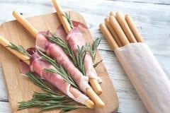 Breadsticks zawijający w baleronie obraz stock