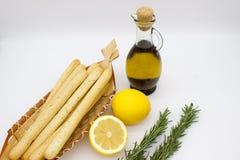 Breadsticksgrissini op rieten plaat, citroenen, en olijfolie stock fotografie