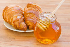 Breafast用新月形面包和蜂蜜 免版税库存照片