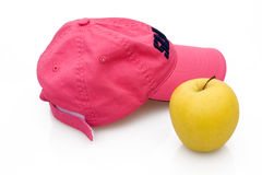 Break. Abstract And Concepts - Taking a break. Pink cap and golden apple Royalty Free Stock Images