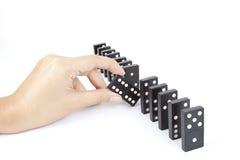 Break. A hand breaking dominos line Stock Photos