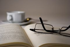 On a break. Glasses on a open book with cafee cup in the background Royalty Free Stock Photos