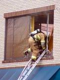 Break In. Fire fighter entering smoldering room through a broken window Stock Photos
