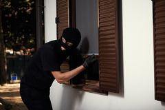 Break-in of an apartment. Thief in mask. Opening the window royalty free stock photography