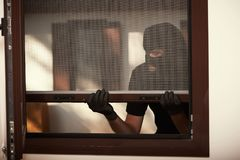 Break-in of an apartment. Thief in mask. Opening the window royalty free stock photo