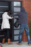 Break-in attempt. A robber attempting to break into a woman's house Royalty Free Stock Image
