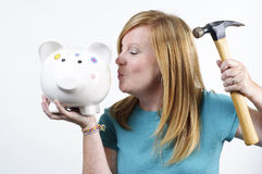 Break the bank. A woman with a hammer ready to break her piggy bank Stock Image