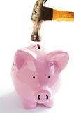 Break the bank. Piggy bank and hammer closeup on white Stock Photos