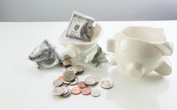 Break the Bank. Broken piggy bank and money Royalty Free Stock Photo