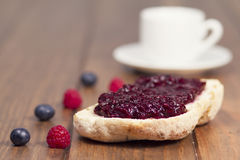 Break with blueberries and raspberries jam. A cup, some blueberries and raspberries and a slice of white bread with jam on a wooden table. Vintage style Stock Image