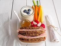 Break bread box with fresh vegetables and ham sandwich royalty free stock photography