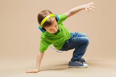 Break dance kids. little break dancer showing his skills in danc. E studio. Hip hop dancer boy in headphones with smartphone against studio background Royalty Free Stock Photography