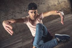 Break Dance. Young man break dancing on the wall background, performing tricks royalty free stock photos