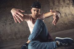 Break Dance. Young man break dancing on the wall background, performing tricks stock photography