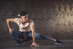 Break Dance. Young man break dancing on the wall background, performing tricks stock image