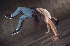 Break Dance. Young man break dancing on the wall background, performing tricks stock photos