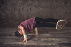 Break Dance. Young man break dancing on the wall background, performing tricks royalty free stock photography