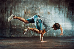 Break dancing man. Young strong man break dancing on old wall background royalty free stock images