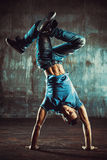 Break dancing. Young man break dancing on old wall background. Vintage film style colors stock photos
