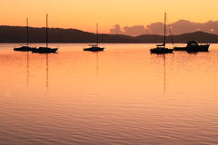 Sailing boat silhouettes at lake by dawn  Royalty Free Stock Photos