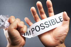 Break down the impossible. Clasping paper, and doing the impossible stock photos