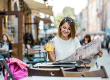 Break with Drink in a Street Cafe. Pretty fair hair caucasian tourist girl with sunglasses on her head is having break with lemonad drink and city map in a Stock Photography