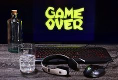 A break at the end of the game. Game, player, keyboard, mouse, headphones, fun, online, drink, glass, bottle, technology, connection, equipment, video game Royalty Free Stock Photo
