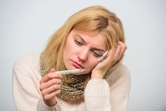Break fever remedies. Take temperature and assess symptoms. High temperature concept. Woman feels badly ill sneezing. Girl in scarf hold thermometer and tissue stock photos