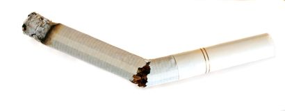 Break free. A lit, broken cigarette, symbolising breaking free of the addiction royalty free stock images