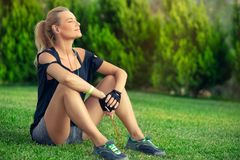 Break after good workout. Beautiful athletic woman resting on green grass lawn after a good workout, tanning and enjoying music, harmony and soul balance concept stock image