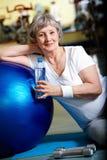 Break in gym. Senior woman having break after exercises Stock Images