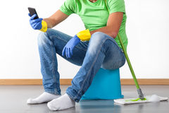 Break during housework. Man sitting on bucket and having break during housework stock photos