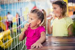Break and ice cream. Two little girl eating ice cream together in park. Close up. Space for copy stock images
